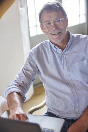 silver surfer: Portrait smiling senior man using laptop