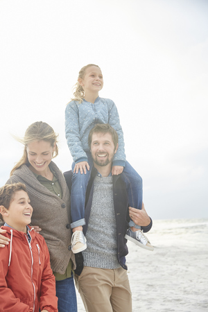 girls at the beach series: Smiling family walking on winter beach LANG_EVOIMAGES