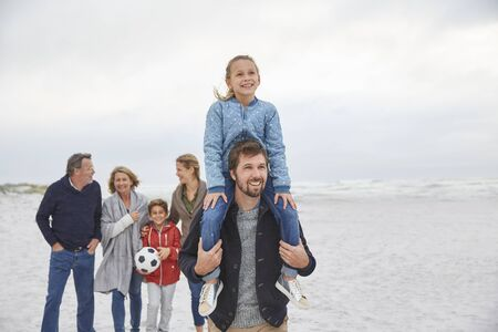 girls at the beach series: Multi-generation family walking on winter beach LANG_EVOIMAGES