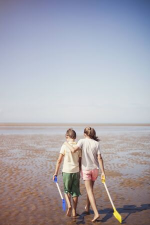 girls at the beach series: Brother and sister with shovels hugging and walking in wet sand on sunny summer beach below blue sky