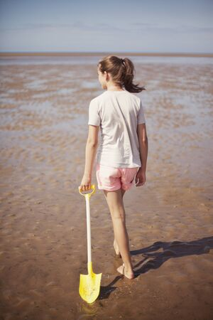 girls at the beach series: Teenage girl dragging shovel in wet sand on sunny summer beach LANG_EVOIMAGES