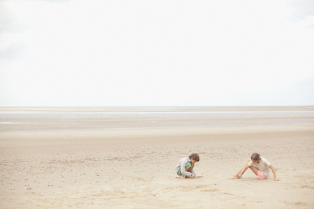 girls at the beach series: Brother and sister playing in sand on overcast summer beach