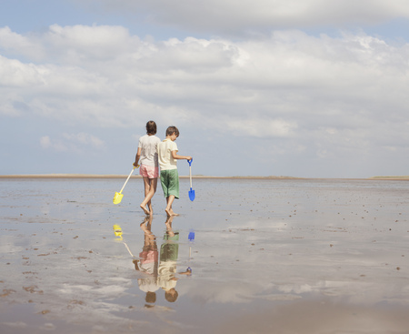 girls at the beach series: Brother and sister walking with shovels in wet sand on sunny summer beach