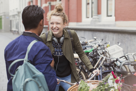 further: Young man and woman with bicycle laughing on city street