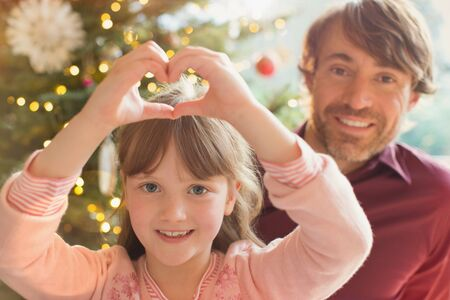 Portrait smiling father and daughter forming heart-shape near Christmas tree
