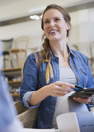 plied: Smiling pregnant woman shopping, paying with credit card in shop LANG_EVOIMAGES