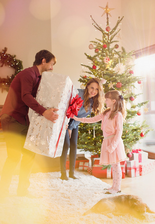 generosidad: Parents giving large Christmas gift to daughter in living room next to Christmas tree