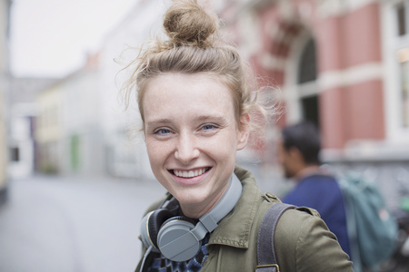 Portrait smiling young woman with headphones on city street LANG_EVOIMAGES