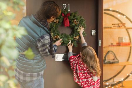 Hängender Weihnachtskranz des Vaters und der Tochter an der Haustür LANG_EVOIMAGES