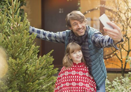 Father and daughter taking selfie with Christmas tree outside of house LANG_EVOIMAGES