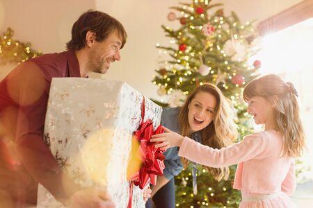 generosidad: Padres dando un gran regalo de Navidad a su hija cerca del árbol de Navidad