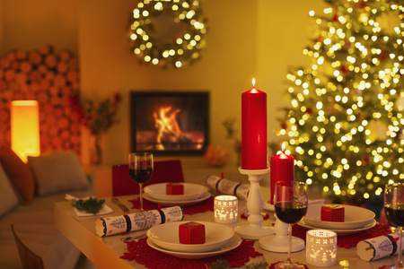 Ambient candles and Christmas crackers on dinner table in living room with fireplace and Christmas tree