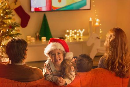 Portrait smiling girl in Santa hat watching TV with parents in Christmas living room