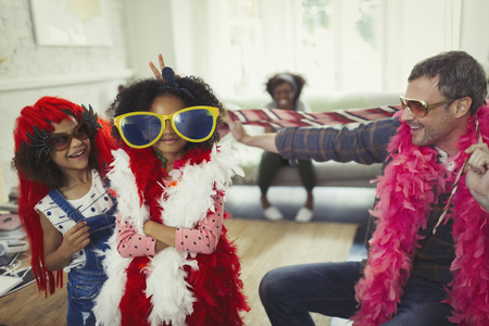boas: Portrait father and daughters playing dress up with oversized sunglasses and feather boas