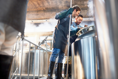 incidental people: Male brewers checking vat in brewery LANG_EVOIMAGES