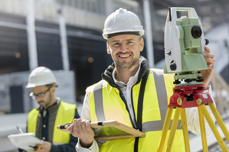 Portrait smiling male engineer using theodolite at construction site