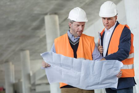 waist down: Male engineers examining underground blueprints at construction site