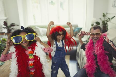 boas: Playful multi-ethnic father and daughters playing dress up with oversized sunglasses and feather boas