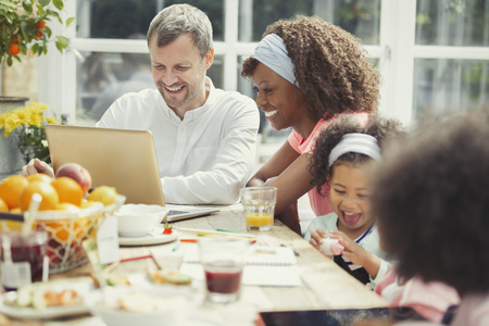 mid morning: Smiling young multi-ethnic family using laptop and eating breakfast at table LANG_EVOIMAGES