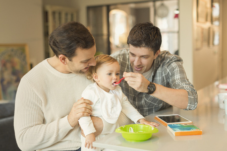 adult sex: Male gay parents feeding baby son in kitchen