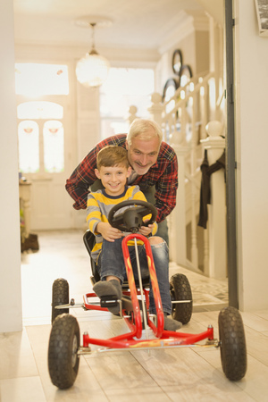 Father pushing son on toy car in foyer corridor