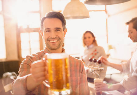 alcohol series: Portrait smiling man toasting beer stein in bar