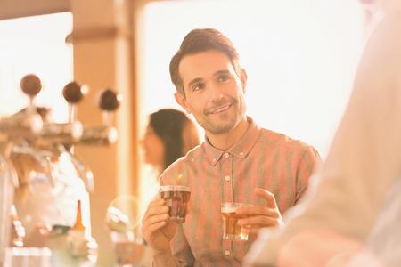 alcohol series: Smiling man sampling beer at bar LANG_EVOIMAGES