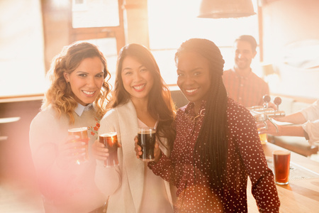 alcohol series: Portrait smiling women friends drinking beer in bar