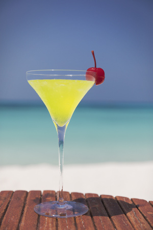 alcohol series: Yellow cocktail with cherry in martini glass on sunny tropical ocean beach LANG_EVOIMAGES
