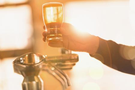 Bartender serving golden pint of beer at beer tap LANG_EVOIMAGES