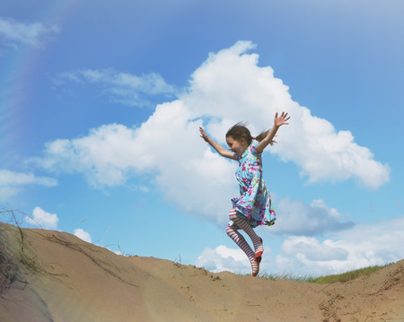 girls at the beach series: Exuberant girl jumping for joy on beach hill below sunny blue sky with clouds