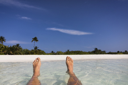 personal perspective: Personal perspective barefoot man floating in tropical ocean surf with view of beach