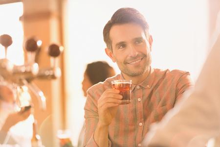 alcohol series: Smiling man drinking cocktail at bar