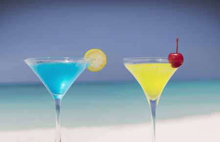 alcohol series: Blue and yellow cocktails in martini glasses on tropical beach