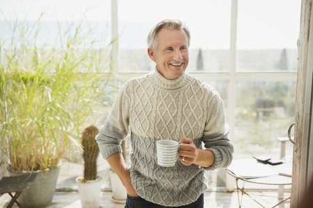 sunroom: Smiling mature man drinking coffee on sunny beach house sun porch LANG_EVOIMAGES