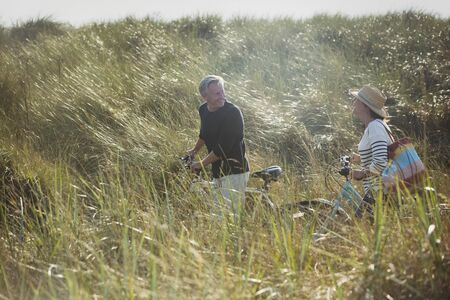 turn away: Mature couple walking bicycles in sunny beach grass