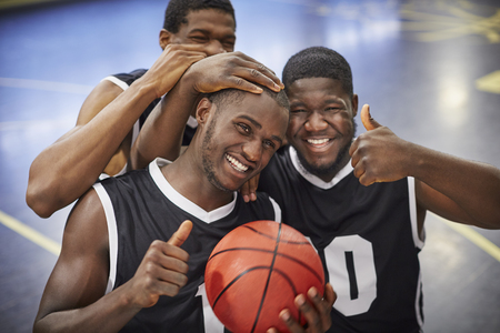 Portrait smiling, confident young male basketball player team celebrating, gesturing thumbs-up LANG_EVOIMAGES