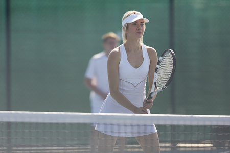 Focused young female tennis player ready with tennis racket at net