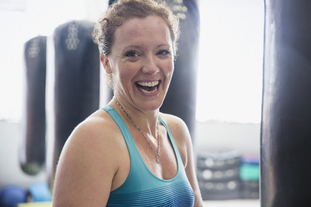 Portrait laughing female boxer standing at punching bag in gym