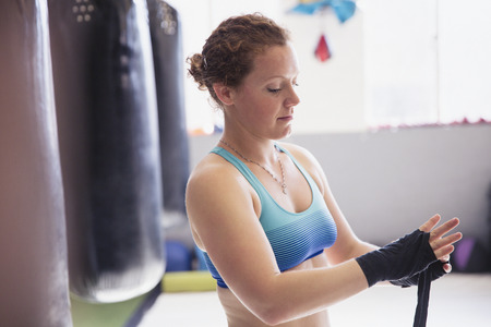Female boxer wrapping wrists next to punching bag in gym