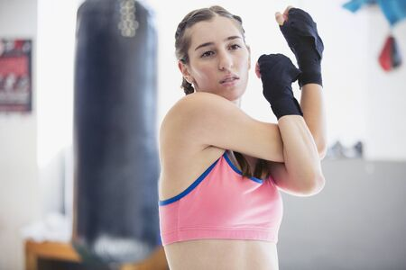 Young female boxer stretching shoulder and arms in gym