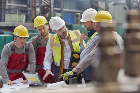 Male foreman, engineers and workers at laptop meeting, discussing blueprints in factory