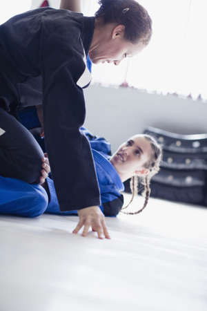 Determined, tough women practicing judo in gym