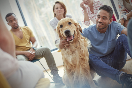 Man petting dog in group therapy session