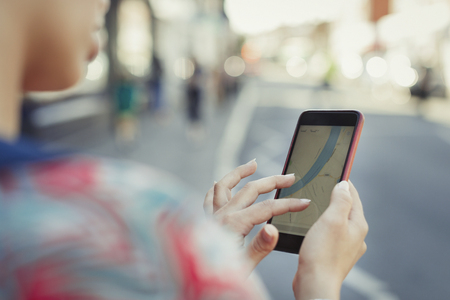 Close up woman using smart phone GPS on street LANG_EVOIMAGES