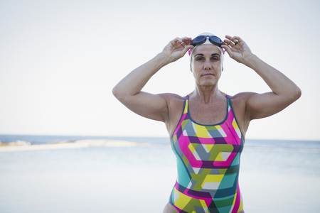 Portrait serious, tough mature female open water swimmer adjusting swimming goggles at ocean