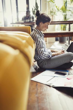 Female freelancer working at laptop on living room floor