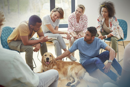 People petting dog in group therapy session LANG_EVOIMAGES