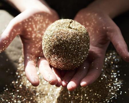 Hands cupping golden glitter apple LANG_EVOIMAGES