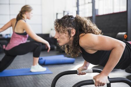 Determined young woman doing push-ups with equipment in gym LANG_EVOIMAGES